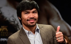 """(FILES) In this September 3, 2014 file photo, Filipino boxing star Manny Pacquiao gestures on arrival for a press conference with fellow boxer Chris Algieri in Los Angeles, California. Pacquiao called his boxing showdown with Floyd Mayweather """"the fight of my life"""" as he got down to work pounding the streets and gym in Los Angeles. The eight-division world champion cranked into serious preparations for the May 2 fight after flying in for his training camp from his native Philippines. On March 2, 2015, Pacquiao ran two miles (3.2 km) and shadow-boxed for two rounds, followed by abdominal work and breakfast of steamed rice, scrambled egg, fish and chicken broth. AFP PHOTO / FREDERIC J. BROWN / FILESFREDERIC J. BROWN/AFP/Getty Images"""